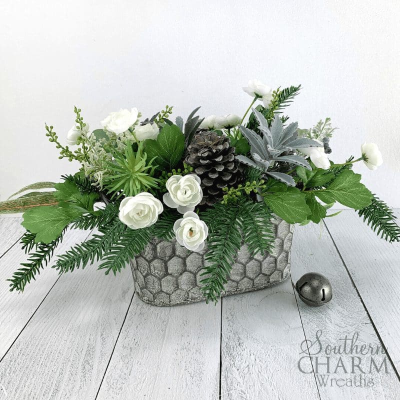 Rustic winter floral arrangement for table centerpiece. Metal honeycomb basket with pine, greenery, succulents, and white flowers.
