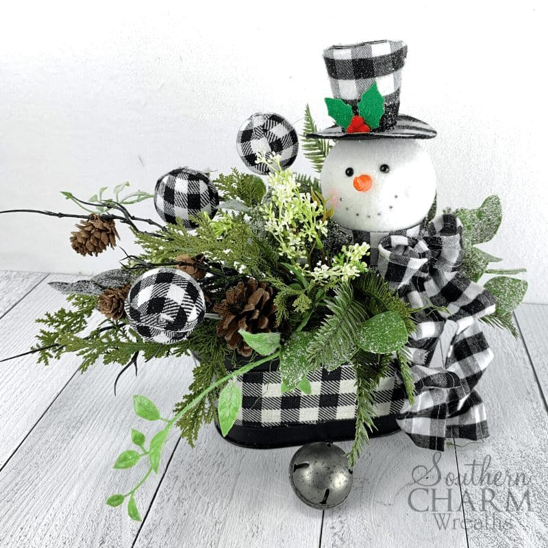 Tabe arrangement with buffalo plaid ornaments and snowman, pinecones and greenery