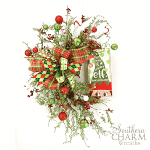 Red and green christmas wreath with ornaments, berries, and elf sign