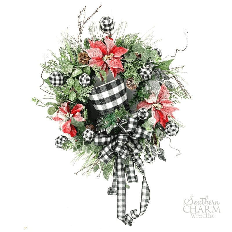 """DIY Carolina Pottery Christmas Snowman Hat Wreath"" - wreath with frosted greenery, poinsettias, pinecones, and black and white buffalo plaid snowman hat with bow and christmas ornaments"