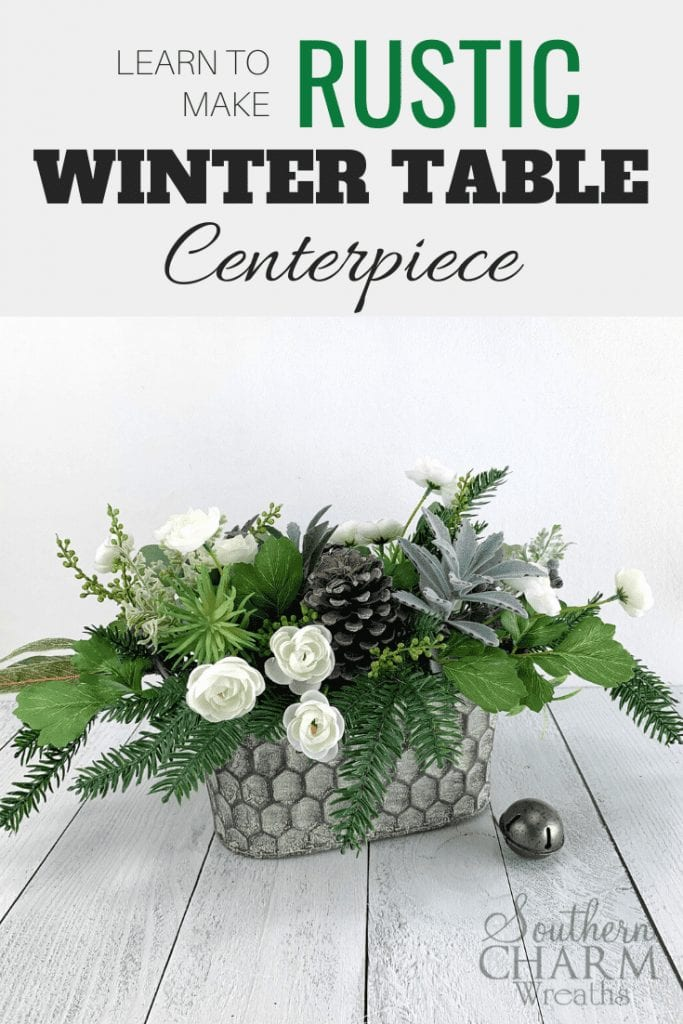 """""""Learn to make a Rustics Winter Table Centerpiece"""" Rustic winter floral centerpiece. Metal honeycomb basket with, greenery, pinecones, succulents, and white flowers."""