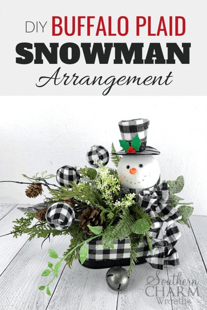 """""""DIY Buffalor Plaid Snowman Arrangement."""" Table centerpiece with buffalo plaid snowman and ornaments, with pinecones and greenery."""