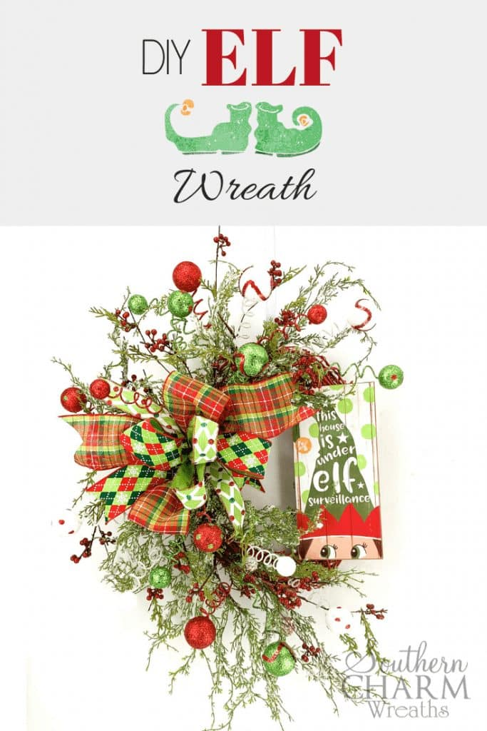 """DIY Elf Wreath"" Bright red and green wreath with elf sign, bow, berries and Christmas ornaments"
