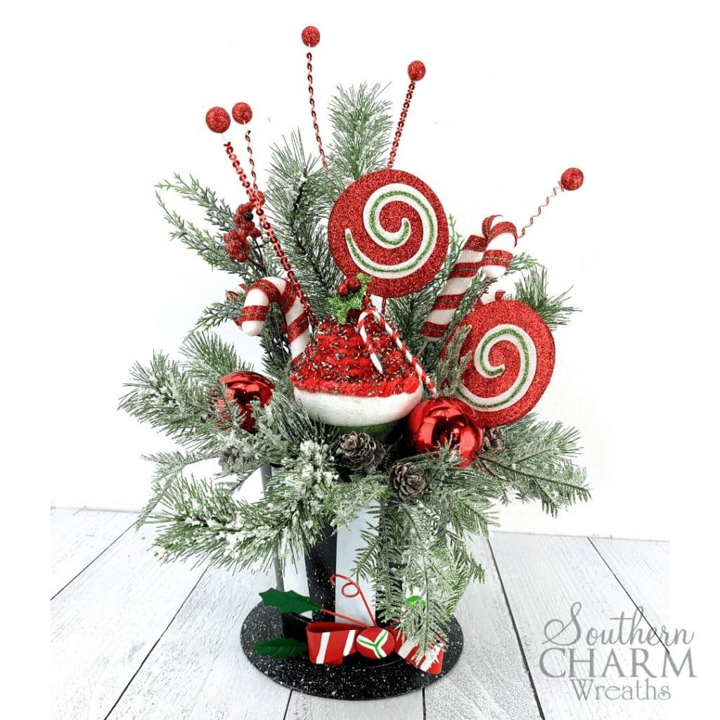 Christmas table arrangement with snowman hat, evergreens, and large candy ornaments