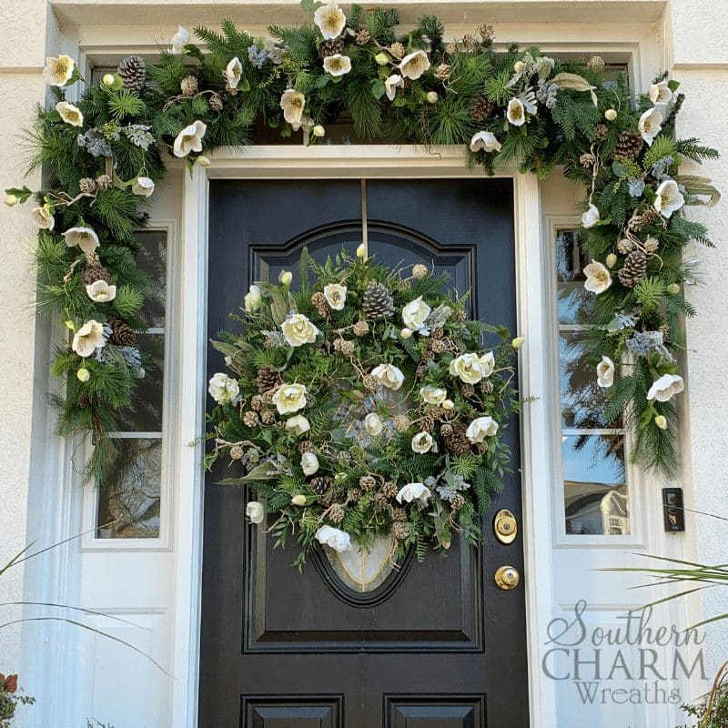 Winter front doorscape with evergreen garland, silk flowers, and pinecones.