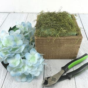 prepping a floral arrangemtn container with foam and moss