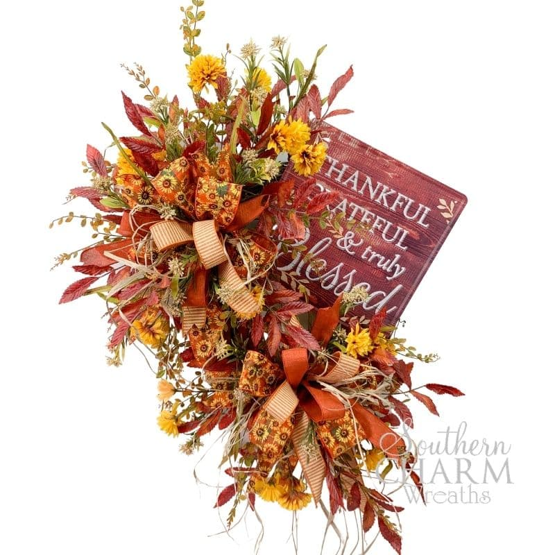 DIY fall wreath with ribbons, flowers, sign