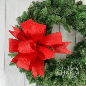 red christmas bow on green wreath