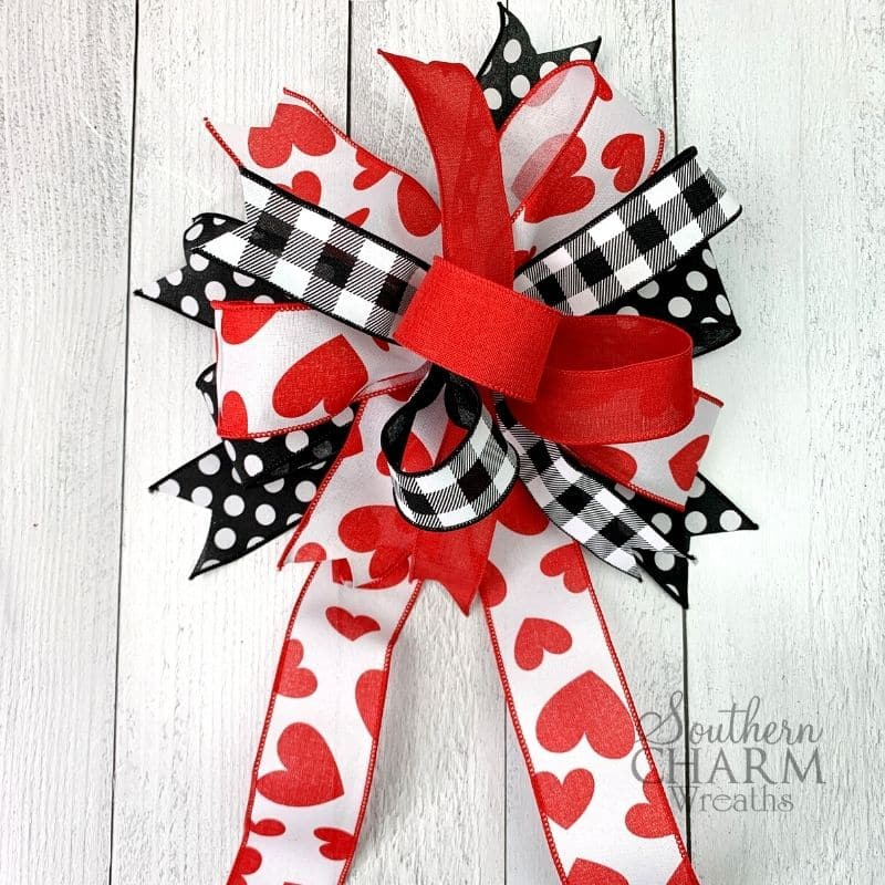 Multi ribbon bow with red ribbon, black and white checkered ribbon, ribbon with red hearts, and black and white polka dot ribbon