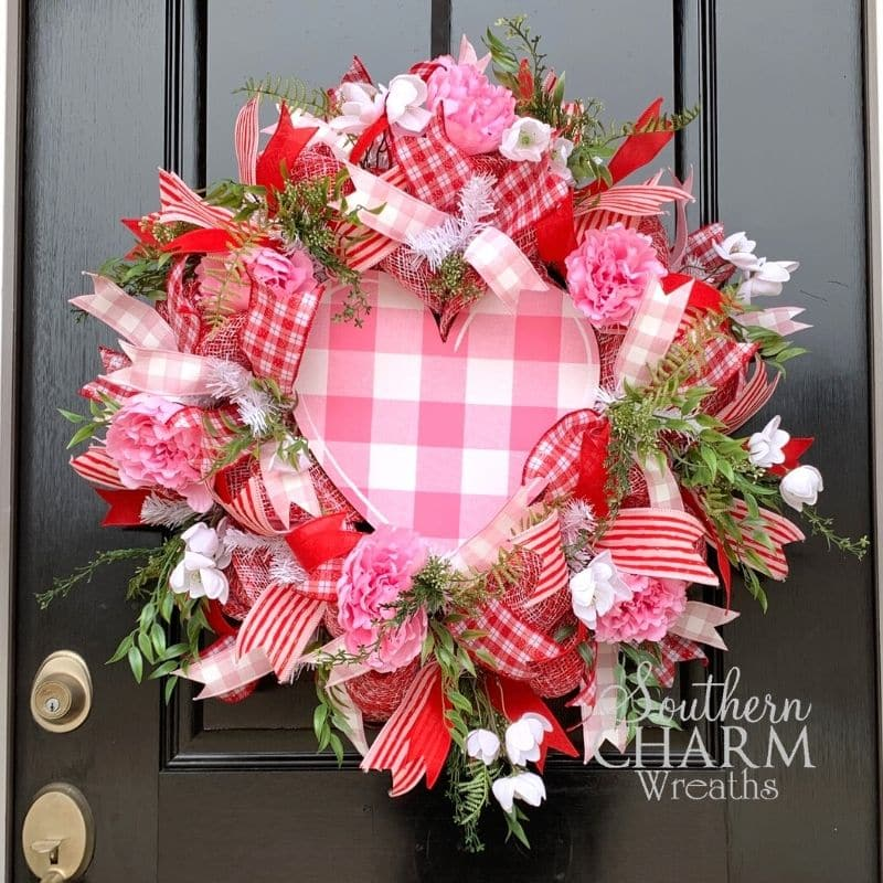 Red, pink, and white deco mesh Valentines day wreath with heart sign on front door
