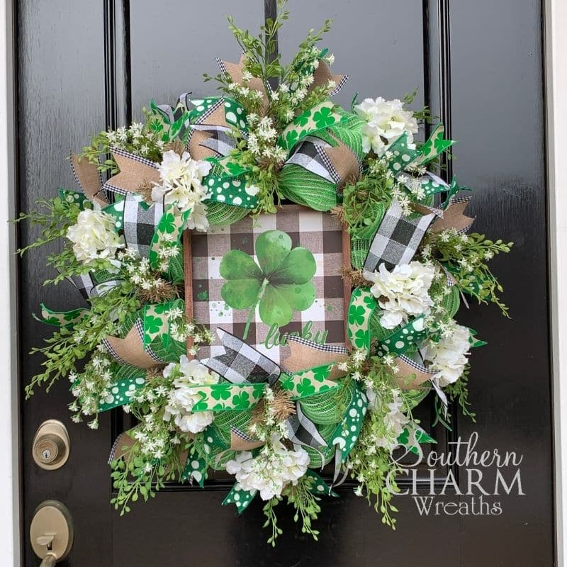St. Patrick's Day deco mesh wreath with white hydrangeas and clover sign hanging on a door