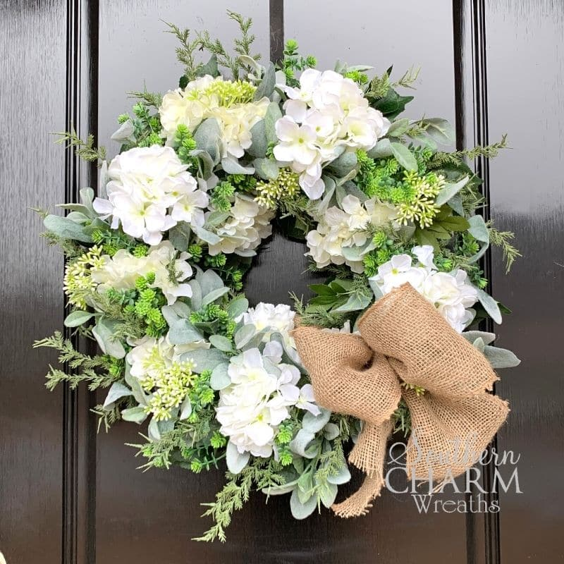 A wreath with greenery, white flowers, and a burlap ribbon