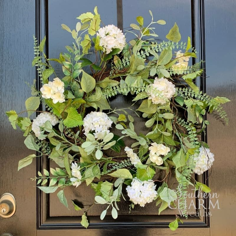 A spring wreath on a front door with white flowers