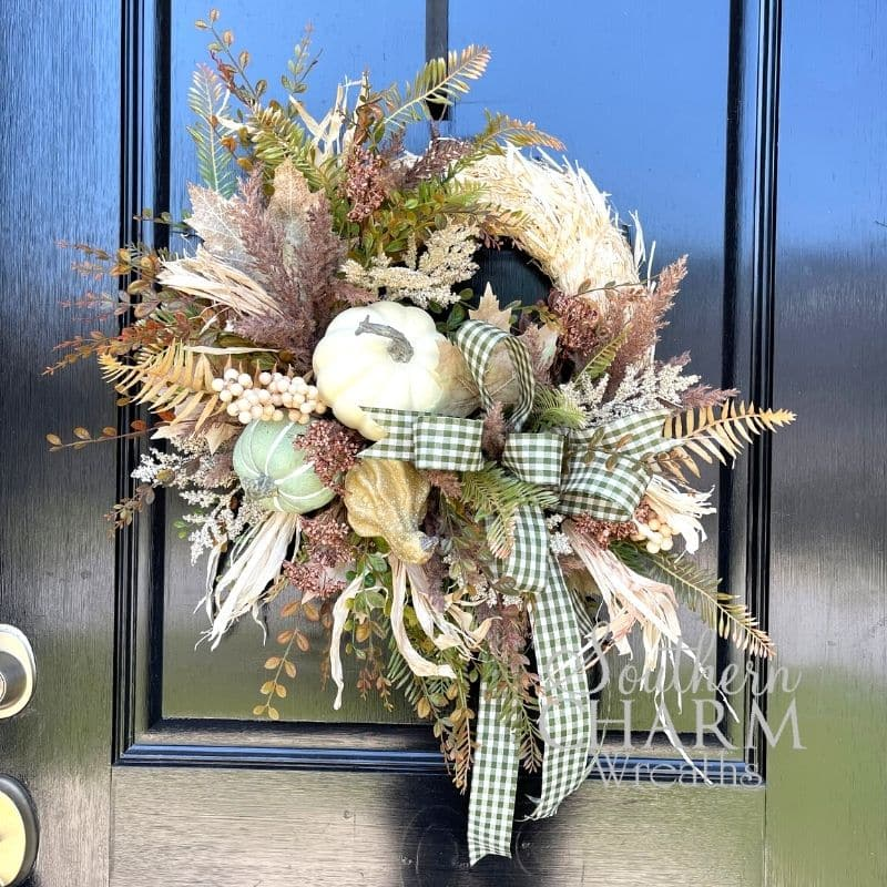 A designer fall wreath on a straw base hanging up on a front door.