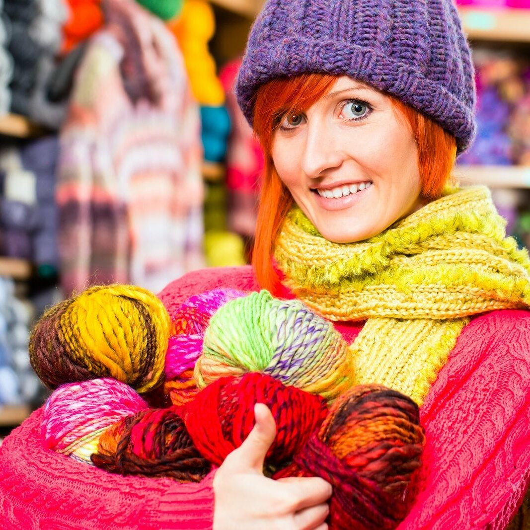 Young woman buying colorful wool and yarn for their hobby in a k